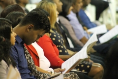 Audience members peruse the graduation booklet